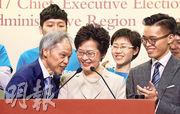 候任特首林鄭月娥(前中)昨日提到,丈夫林兆波(前左)為她犧牲了很多,說時轉頭向丈夫道歉,「對不起啊老公,你要繼續犧牲……繼續犧牲」。林兆波此時插話「我樂意為香港市民作犧牲」,長子林節思(前右)與競選團隊隨即拍掌。(曾憲宗攝)