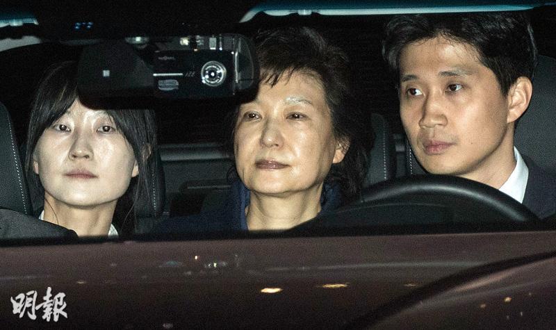 法官周五凌晨下令拘捕朴槿惠(中),檢察搜查官隨即押送朴槿惠離開首爾的中央檢察辦公室前往首爾拘留所。(新華社)