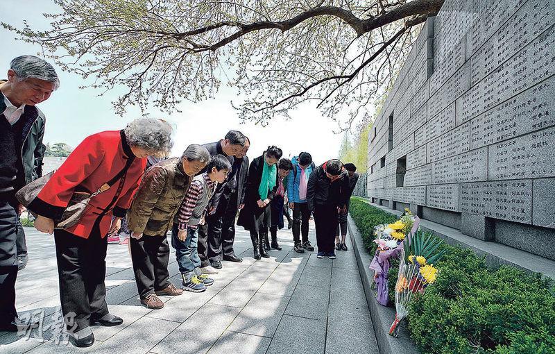 清明將至,江蘇南京侵華日軍南京大屠殺遇難同胞紀念館迎來眾多憑弔者,倖存者李美蘭(左三)及家人昨在侵華日軍南京大屠殺遇難同胞紀念館「哭牆」前鞠躬默哀。(新華社)