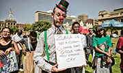 周一在南非財政部外的反祖馬示威中,有男子喬裝小丑帶上標語稱「祖馬不是小丑。小丑不會在應該哭的時候傻笑」。(法新社)