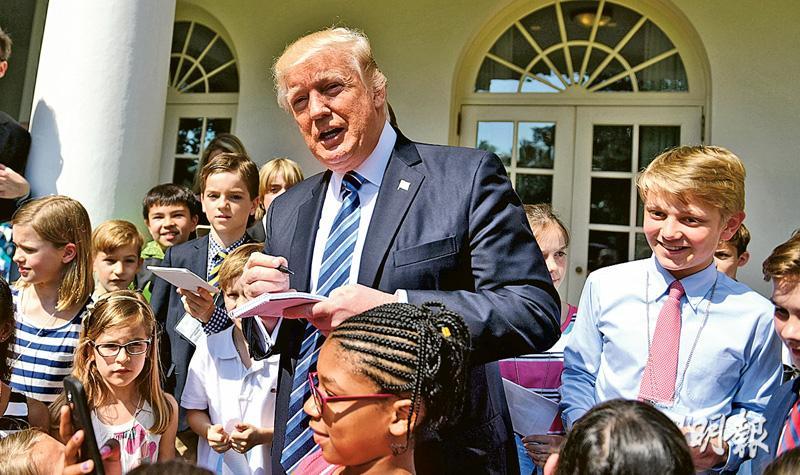 白宮周四舉行一年一度的「帶孩子上班日」,總統特朗普(中)為到白宮參觀的孩子簽名。(新華社)
