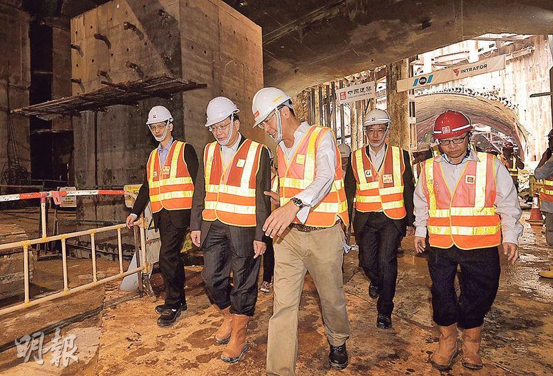 路政署表示,港珠澳大橋香港接線觀景山隧道段最後一件重約5000公噸的隧道預製組件,周二成功推進位於機場快線下方的最終位置,觀景山隧道內所有挖掘工程亦已完成,令香港接線正式全線貫通。運輸及房屋局長張炳良(左二)昨到工地視察,他稱現有成果得來不易。(中通社)