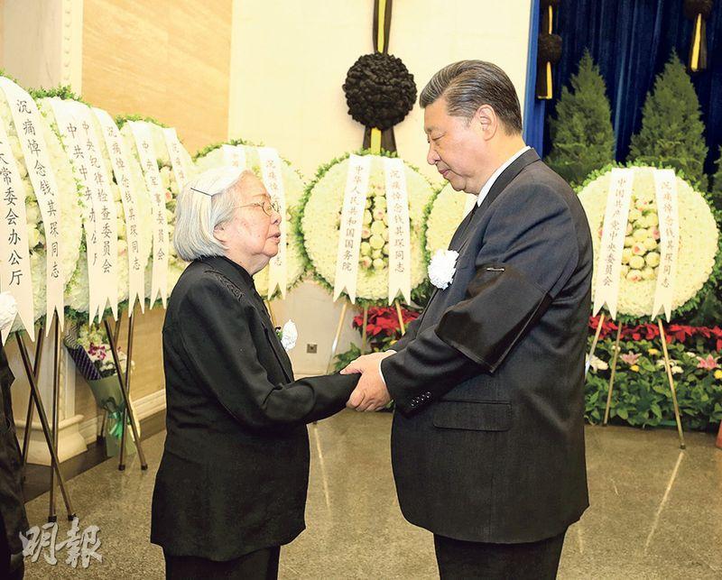國家主席習近平(右)與錢其琛遺孀周寒瓊握手,表示深切慰問。(新華社)
