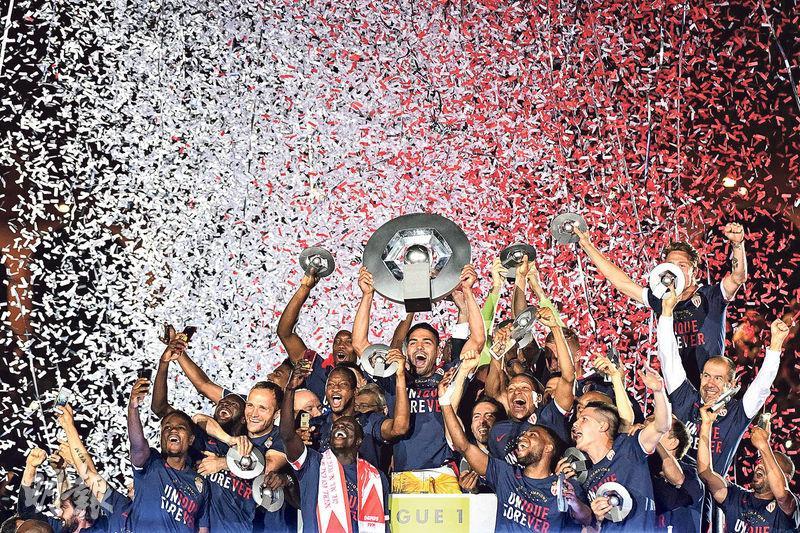 今季重拾昔日「虎威」的摩納哥隊長法卡奧(捧盃者),率領眾將舉起法甲冠軍寶座。(法新社)