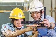 建造業議會基本工藝課程水喉潔具科畢業生黃雪凝(左)今年將代表香港參加世界技能大賽的水喉比賽項目,建造業議會工藝導師(水喉潔具科)鄧志偉(右)指出,除了需一定體力,亦講求技巧,才可精準扭出角度和形狀合適的水喉。(楊柏賢攝)