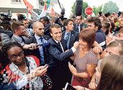 法國總統馬克龍(中)上周五到上維埃納省,探訪面臨破產倒閉危機的汽車供應商GM&S,與廠房工人會面,為國會選舉拉票。(法新社)