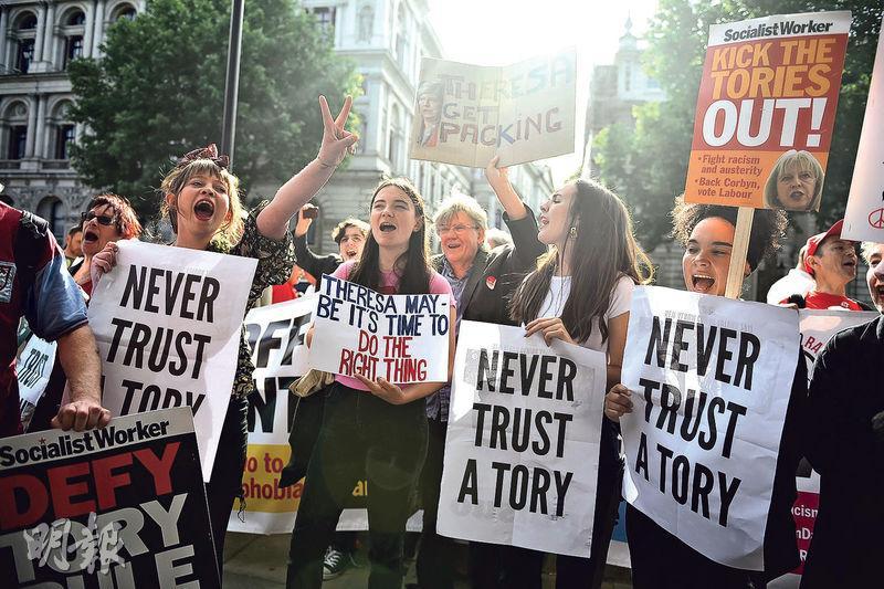 保守黨經歷大選意外失利後,有示威者再到唐寧街外抗議,高舉「永不要信任保守黨」的標語。(路透社)