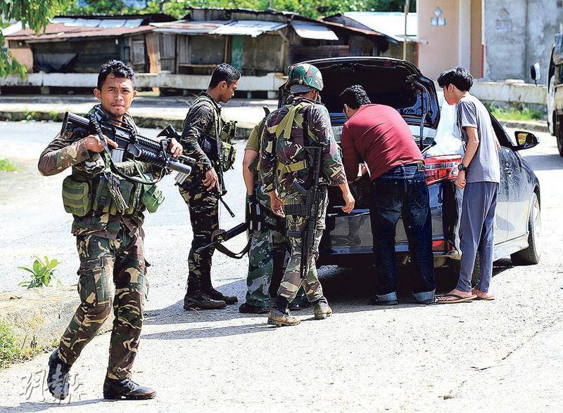 菲律賓士兵昨日在馬拉維市一個檢查站查車。他們持續在菲南搜捕、攻擊「毛特組織」成員。(路透社)