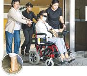 因接受涉案療程導致需截去一雙小腿及右手4隻手指(小圖)的王靜波(前),現時雙腿相信是裝上義肢,要靠輪椅出入。她表示事發後記憶力及聽力衰退,原本任職小學教師的她,事後不獲學校續約。(楊柏賢攝)