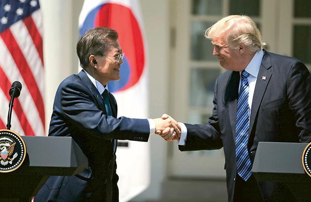 美國總統特朗普(右)和韓國總統文在寅(左)昨日在白宮於會談後的聯合記者會上握手。(路透社)