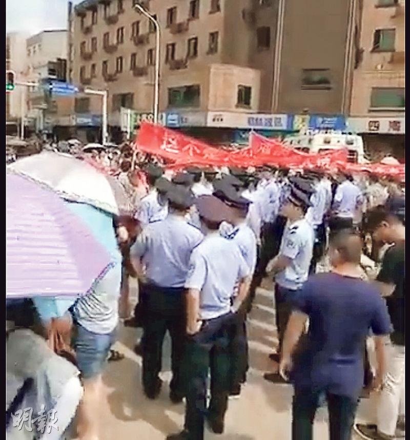 湖南寧鄉洪水災民一連兩日聚集於縣內示威,拉起寫上「這不是天災 而是人禍」的標語,有城管人員在場監視。(網上圖片)