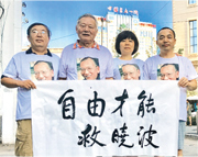 內地維權律師丁家喜(右)和友人身穿印有劉曉波頭像的T恤,手持橫額在醫院前為劉曉波打氣。(網上圖片)