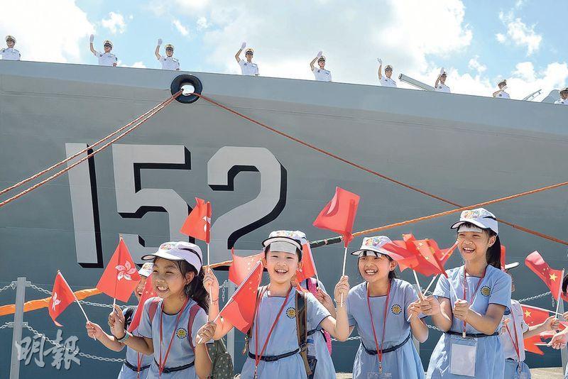 逾60名來自旅港開平商會學校的小學生獲邀到昂船洲軍營參加歡送儀式。有學生表示跟隨老師到場,並獲派退熱貼散熱,以防中暑。後方的士兵站在導彈驅逐艦「濟南號」甲板上,向市民揮手道別。(鍾林枝攝)