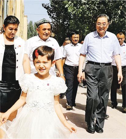 出席第六次全國對口支援新疆工作會議期間,中共中央政治局常委俞正聲(右)還到民族團結小區調研。(新華社)