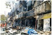 發生爆炸的店舖燒至牆身焦黑,圖為消防在清理火場。(網上圖片)