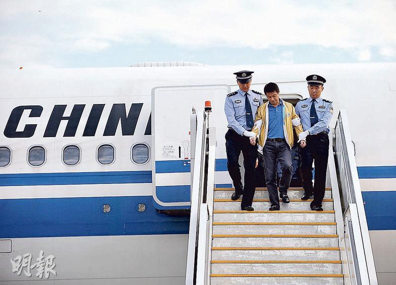 「百名紅通人員」任標昨日回國投案。圖為任標(中)在警方押送下走出機艙。(新華社)