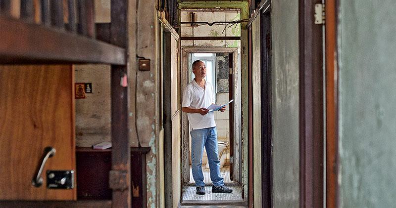 一直關注劏房住戶的社協主任何喜華手執圖則,由社工變身單位管理者,處理單位內一磚一瓦的擺位;面對空置破落的單位,他說需要更多有心有力的人投入協助。(鄧宗弘攝)