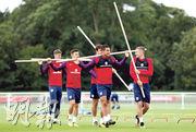 英格蘭前鋒占美華迪(右一)及中場積基李華摩亞(右二)與隊友一起手持竹竿準備練習,狀甚輕鬆。(路透社)