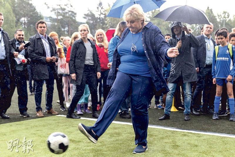 挪威首相索爾貝格(前)上周六在奧斯陸的保守黨競選活動中踢足球。(法新社)