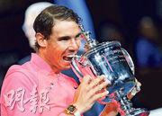 31歲的拿度繼2013年後,第3次贏得美網錦標,昨賽後以招牌式咬獎盃慶祝,亦是他第16項大滿貫錦標。(新華社)