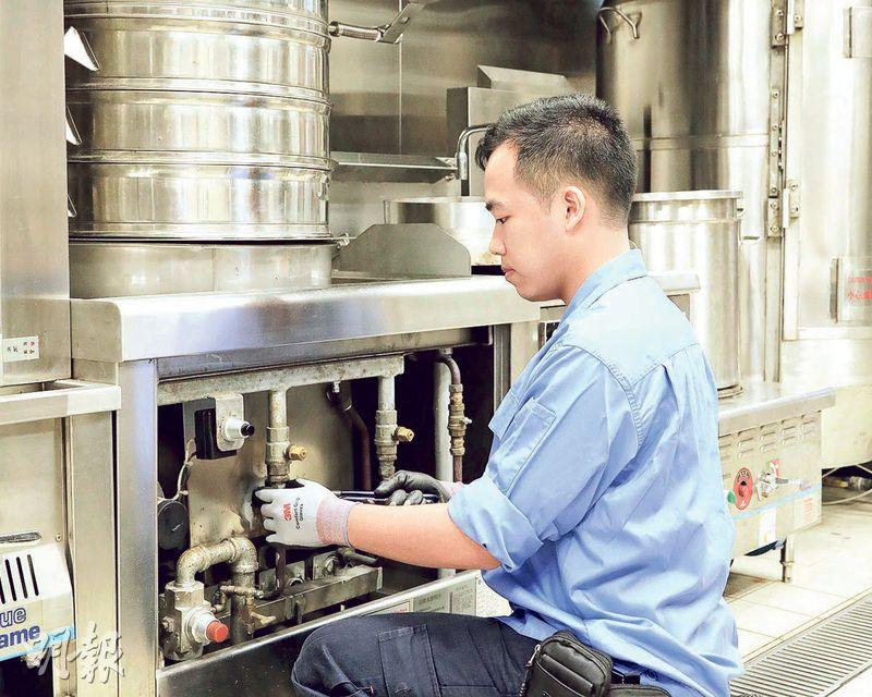 邱敬霖回想文憑試放榜前,有學長建議他學一門手藝,修讀氣體工程。他了解課程內容後,認為自己性格正好符合工作需要。圖為他在商業廚房檢查煤氣爐具,少一點細心和耐性都不行呢。