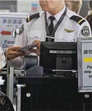 機場前晚揭發懷疑監守自盜案件,一名保安執勤期間疑偷取旅客銀包內1300元人民幣(約1500港元),涉嫌盜竊被捕。圖為機場保安日常為旅客檢查證件情况。(資料圖片)