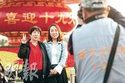 十九大前夕的北京市面氣氛有如過節,圖為遊客在天安門廣場上的「喜迎十九大」巨型花籃前留影。(明報記者攝)
