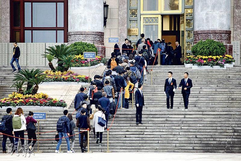 記者昨日進入大會堂參加記者會,手上的證件和請柬要經過多次查驗。(明報記者攝)