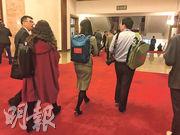 多名記者即時使用大會放發的背包,也不介意與同行撞款。(明報記者攝)