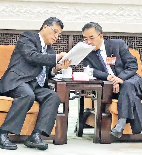 廣東代表團昨日開放,廣東省委書記胡春華(右)和省長馬興瑞(左)在討論報告。(明報記者攝)