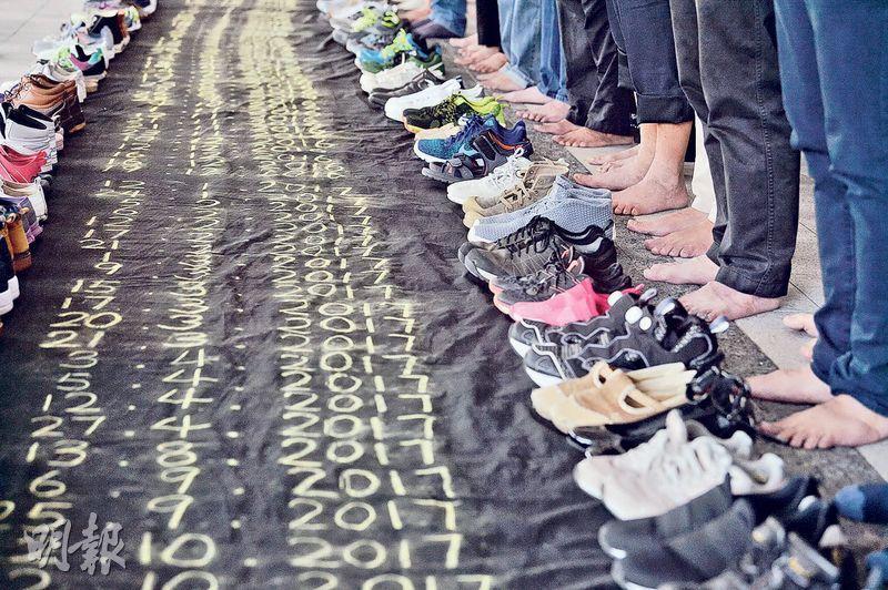 有團體昨日發起遊行,要求政府正視學生自殺問題,遊行人士把「孩子」(鞋子)放在地上一幅寫上學生自殺日期的布幡上悼念,然後赤腳遊行至特首辦。(馮凱鍵攝)