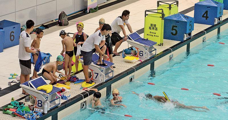 本報記者昨於維多利亞公園游泳池,見駐場泳會租用泳線開泳班教導參與小學生習泳計劃的幼童,學員均戴上隨計劃附送、有賽馬會標誌的黃色泳帽。(鍾林枝攝)