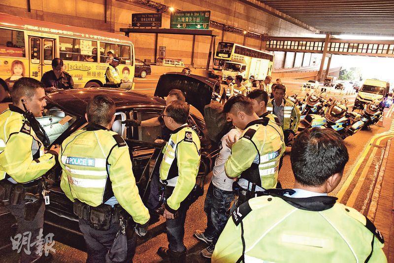 警匪經過約6分鐘追逐,涉案平治房車逃至藍田港鐵站失控撞九巴「拋錨」,司機(白T恤及黑布蒙頭)由趕至警員制服拘捕。(鍾炳然攝)