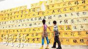 在中國,姓名也有明顯的時代特徵。圖為兩名兒童經過2012年浙江美術館一個書法展的百家姓書法牆。(網上圖片)