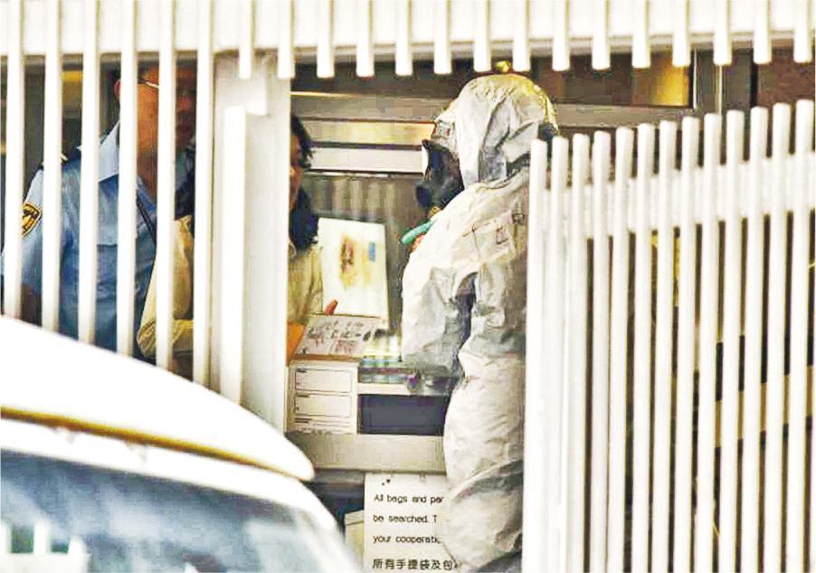 穿戴防毒面罩及防生化裝備保護衣的爆炸品處理課人員,進入美國總領事館檢視職員發現的可疑信件,初步證實無危險成分,用盒將信件載走檢驗。