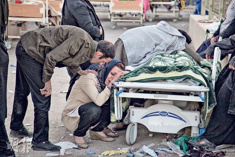 兩伊邊境地區周日發生7.3級地震,造成逾400人死亡。在重災區伊朗薩波勒扎哈布鎮,一名婦人痛哭哀悼死者。(法新社)