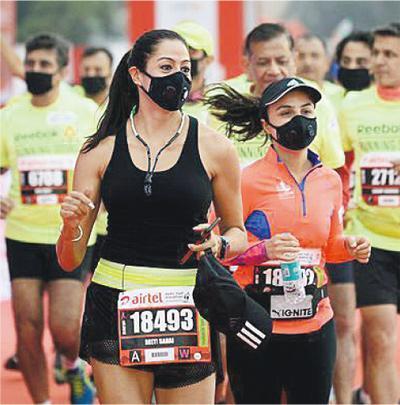 新德里半馬拉松昨日在嚴重霧霾天氣中舉行,不少跑手戴上口罩作賽。(法新社)