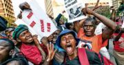 穆加貝辭職消息傳出後,津巴布韋首都哈拉雷大批民眾上街慶祝。圖中右方青年手持發動政變的國防司令奇文加照片,促他當英雄到底。(路透社)