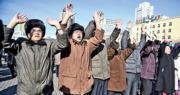 朝鮮民眾昨在平壤火車站外舉手歡呼國家試射「火星-15」洲際導彈成功。 (法新社)