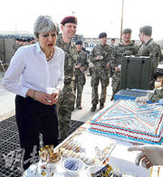 英國首相文翠珊(前左)周三到訪伊拉克,到一個軍事基地探望英兵,其間享用軍營的糕點小食。(路透社)