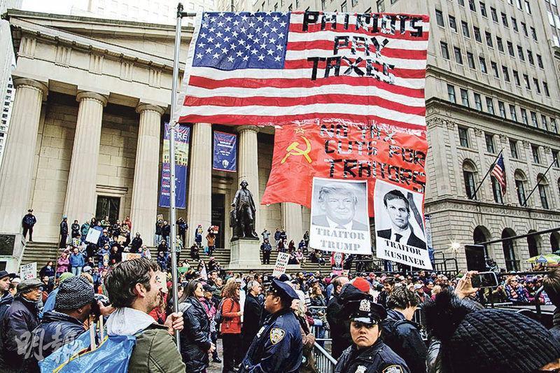 曼哈頓的紐約交易所外前天有示威者舉起特朗普及其女婿庫什納的肖像,抗議特朗普政府推出的稅改方案,以及兩人為主的團隊捲入「通俄」醜聞。(路透社)