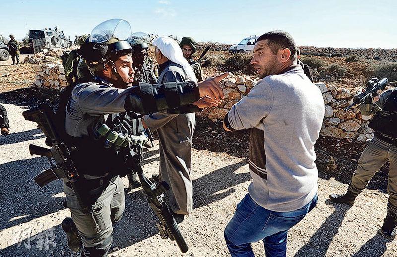 以色列邊境警察昨在約旦河西岸,與巴勒斯坦男子爭拗。(路透社)