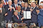 美國總統特朗普(前)周一在猶他州官員簇擁下,展示他所簽署有關大幅削減國家紀念區保護範圍的行政命令。(法新社)