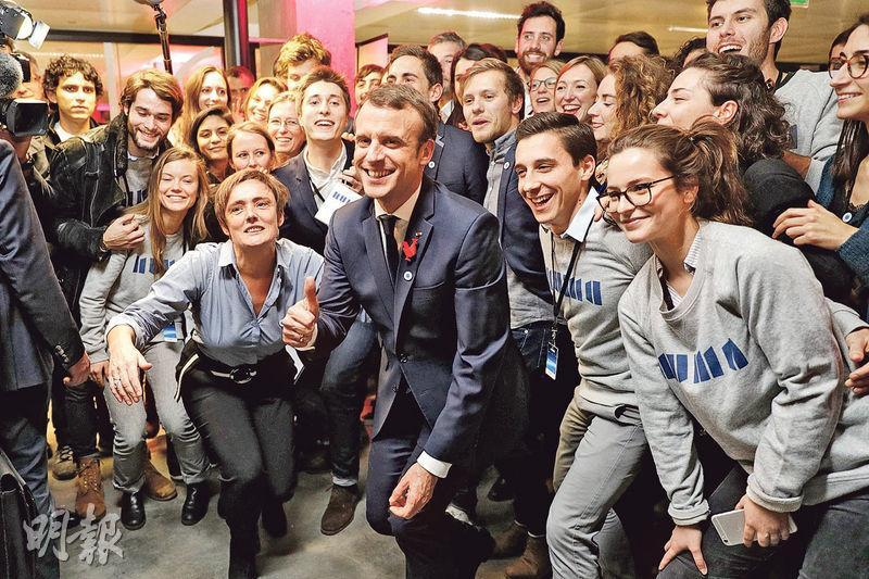 法國總統馬克龍(中)周二在巴黎主持「一個星球」氣候峰會前,與參加環保科技活動的民眾合照。(法新社)