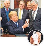 美國總統特朗普(前)周一在白宮簽署「太空政策1號指令」,宣布重返月球和探索火星計劃,其間他拿起一個太空人模型公仔。(法新社)