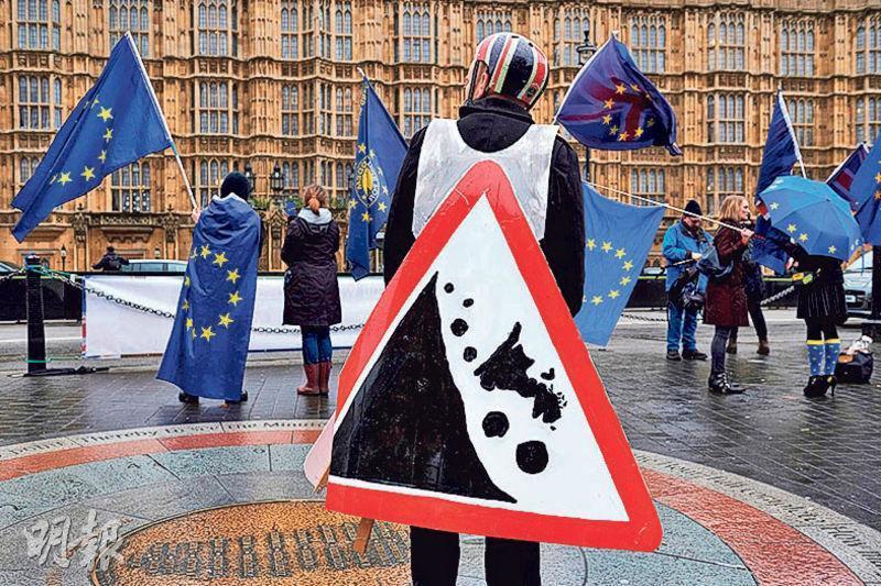 親歐盟反脫歐的示威者周三在下議院外揮舞歐盟旗幟,並展示比喻英國脫歐儼如山泥傾瀉的告示牌。(法新社)