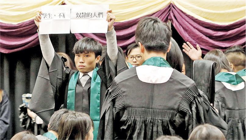 港專學院暨香港專業進修學校昨日舉行畢業禮,今年新增規定要求學生在播國歌時肅立,有學生不遵從,堅持坐下,並有人高舉紙張,上面寫上「學生,不願……奴隸的人們」。
