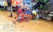棉蘭老島卡加延德奧羅市的道路上周五水深及腰,有民眾擠在一輛車的車頂。(路透社)