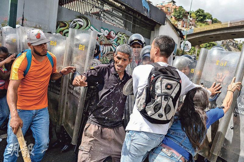 委內瑞拉群眾周四在加拉加斯抗議無豬肉應節,遭防暴警察阻撓。(法新社)