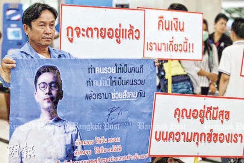 泰國龐氏騙局受害者5月在曼谷特別調查部外舉起標語,促請對主謀普迪(帶眼鏡者)採取法律行動。(網上圖片)